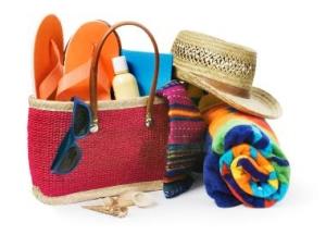 Photo pof beach bag and beach supplies - sunglasses, towels, hat, sun tan lotion