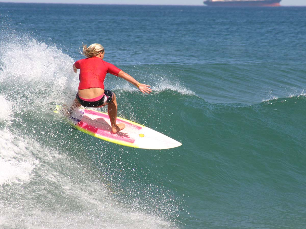 A female surfer competing in a professional surfing competition.